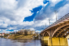 Urban architecture, a bridge in retro style with arched spans and massive yellow supports is reflected in the blue river Stock Photography