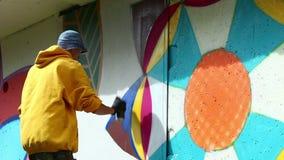 Urban art - guy drawing graffiti on wall stock video footage