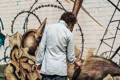 Urban artist drawing graffiti on a wall in Shoreditch. Royalty Free Stock Image