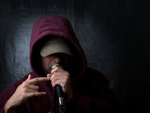 Urban artist - rapper. Rapper wearing hood and singing to a microphone Stock Images