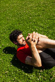 Urban athlete doing stretching exercises on the grass Stock Photography