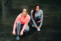 Women ready for running and training under the rain. Urban athletes lacing sport footwear for running over asphalt under the rain. Two women getting ready for Stock Image
