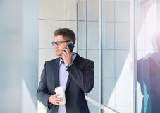 Urban attractive businessman with phone device and coffee on off Stock Images