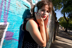 Urban Audio. A vintage dressed girl listing to music in a urban environment Stock Photo