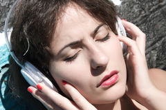 Urban Audio. A vintage dressed girl listing to music in a urban environment Royalty Free Stock Photo