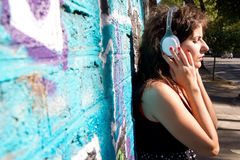 Urban Audio. A vintage dressed girl listing to music in a urban environment Stock Image