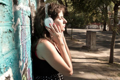 Urban Audio. A vintage dressed girl listing to music in a urban environment Stock Photography