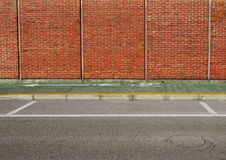 Urban background. Green bicycle lane between a brick wall and the street. Royalty Free Stock Photography