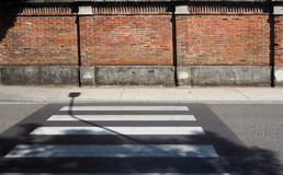 Urban background. Pedestrian crossing and street lamp shadow in front of an old brick wall. Urban background. Zebra crossing and street lamp shadow in front of Royalty Free Stock Photos