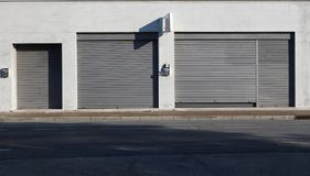Urban background. Shop retail with metal shutters closed on the sidewalk at the side of the road.  royalty free stock photography