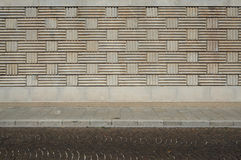 Urban background. Wall with geometric patterns, sidewalk and street with porphyry cubes. Urban background. Wall with geometric patterns, sidewalk and street made Stock Photography