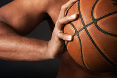 Urban Basket ball. Black male hand clutching a gritty basketball  shallow depth of field with focus on the ball and hand Stock Photo