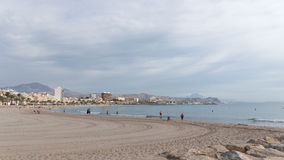 Urban beach of El Campello. El Campello - October 3, 2015: A lovely beach town in the morning and some people relax and bathe in the sea 3 October 2015, El Stock Photos