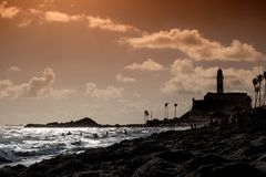 An urban beach in Salvador de Bahia, Brazil just before sunset w. Ith a lighthouse and palm trees in the background. The beach is called praia farol de barra royalty free stock photos