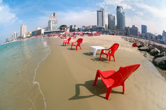Red chairs on the sandy beach. Urban beach in Tel Aviv. Lens Fish eye Royalty Free Stock Image