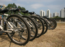 Urban Bike Park. A row of bicycles in a Hong Kong Park, with apartment buildings in the background Stock Image