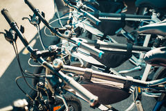 Urban Bikes In A Row. Daily Urban Lifestyle Rent Concept. Urban bicycles for hire standing in a row Royalty Free Stock Photography