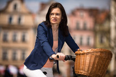 Urban biking - middle-age woman and bike in city Stock Photography