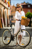 Urban biking - middle-age woman and bike in city Stock Image
