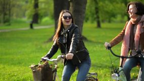 Urban Biking in the Park of Two Pretty Brunettes with Charming Smiles. First Woman has Short Curly Hair, Another One. Wearing Sunglasses, HD stock video footage