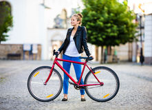 Urban biking - young woman and bike in city Royalty Free Stock Photo