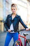 Urban biking - young woman and bike in city Stock Images