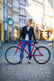 Urban biking - young woman and bike in city Royalty Free Stock Photography