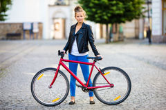 Urban biking - young woman and bike in city Royalty Free Stock Image