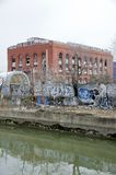 Urban Blight. Abandoned buildings with graffiti and a polluted canal in an urban setting Royalty Free Stock Photos