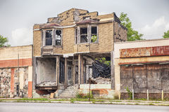 Urban Blight In Detroit. DETROIT, USA - JUNE 9, 2015: A burned out and semi-demolished building between two closed storefronts on Hamilton Avenue in Detroit Stock Images