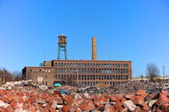 Urban Blight Factory. An empty and crumbling factory is shown  behind piles of lumber and brick rubble in the Wyoming Valley of northeastern Pennsylvania Stock Photo