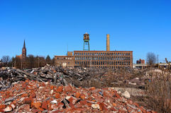Urban Blight Factory. An empty and crumbling factory is shown  behind piles of lumber and brick rubble with a church, a highway and other buildings in the Royalty Free Stock Image