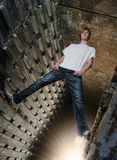 Urban Boy. Surreal picture of a handsome young man in grunge industrial environment, climbed up the walls to the ceiling, looking cool and relaxed. The strange Stock Photography