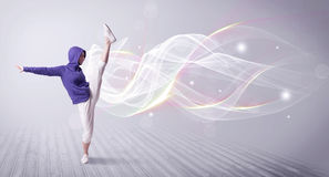 Urban breakdancer dancing with white lines. A beautiful young hip hop dancer dancing contemporary urban street dance in front of grey wall background with smokey Stock Photos