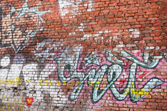 Urban brick wall with grungy chaotic graffiti Royalty Free Stock Photos