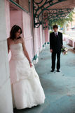Urban Bride and Groom portrait. A portrait of a young bride and groom standing near an old building royalty free stock images