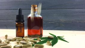 Glass Bottles with CBD Cannabis oil and CBD capsules spill in slow motion on table. Glass Bottles with CBD Cannabis oil and CBD capsules spill in slow motion stock footage