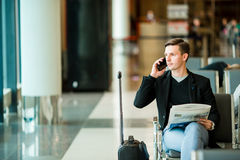 Urban business man talking on smart phone inside in airport. Casual young businessman wearing suit jacket. Handsome male Royalty Free Stock Photography