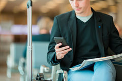 Urban business man talking on smart phone traveling inside in airport. Casual young businessman wearing suit jacket Stock Photo