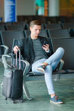 Urban business man talking on smart phone traveling inside in airport. Casual young businessman wearing suit jacket Royalty Free Stock Photos