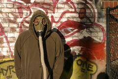 Urban camoflauge. A man in a gas mask trys to hide against an urban graffitti wall Stock Photo