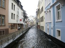 Urban canal, Freiburg, Germany. This canal flows through the city of Freiburg, Germany.  Some windows are only inches above water level Royalty Free Stock Image