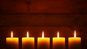 Urban Candles on Vintage Ship Wood Background. This is a video of five candles with flames at the bottom of the frame. They are lit at the beginning stock video