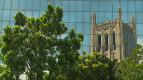 Urban Cathedral Reflection. The reflection of a Victorian Gothic Revival cathedral in the glass windows of a modern building stock video