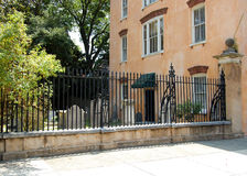 Urban cemetery. View of a house beside a cemetery with old headstones and black metal railings Stock Image