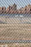 Urban Chain Link Closeup Abstract Texture Background. Chain link fence closeup abstract texture background with urban city skyline background Royalty Free Stock Photo