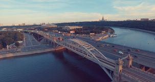 Urban city aerial view. Beautiful Aerial view of Luzhnetsky metro bridge. Flying over heavy traffic in the evening, top view of Moscow river and urban city stock video