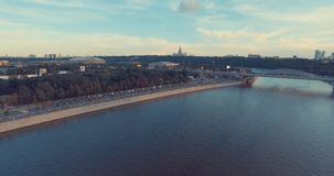 Urban city aerial view. Beautiful Aerial view of Luzhnetsky metro bridge. Flying over heavy traffic in the evening, top view of Moscow river and urban city stock footage