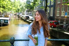 Urban city lifestyle hipster girl drinks green juice on Amsterdam canal, Netherlands. Healthy detox vegan diet with vegetable cold. Pressed extract for smooth royalty free stock images
