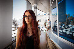 Urban city portrait of girl. Beautiful thinking girl with long red hair and glasses looking aside. Pretty girl in black dress on c Stock Photos